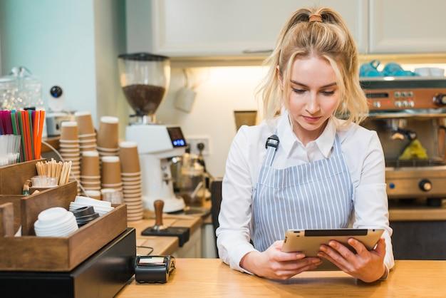 Mujer joven rubia que se coloca en el contador de la cafetería que mira la tableta digital Foto gratis