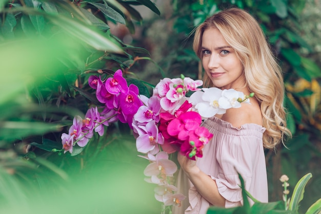Mujer joven rubia que se coloca en el jardín que sostiene la orquídea Foto gratis