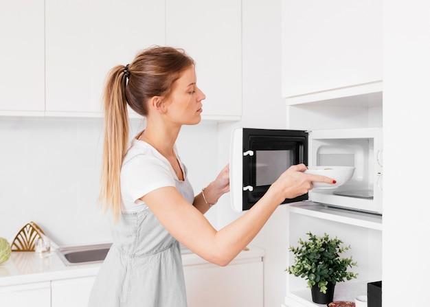 Mujer joven rubia que inserta el cuenco en el horno Foto gratis