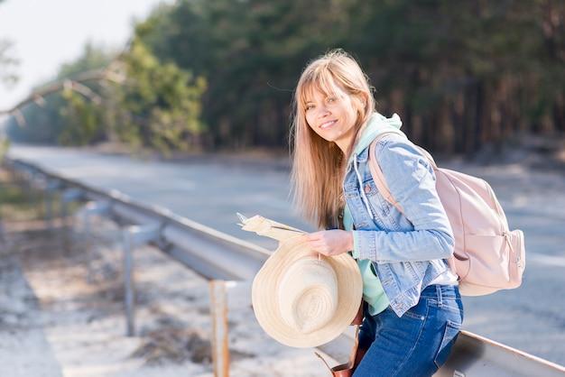 Mujer joven rubia que sostiene el sombrero y el mapa que se colocan cerca del camino con su mochila que mira la cámara Foto gratis