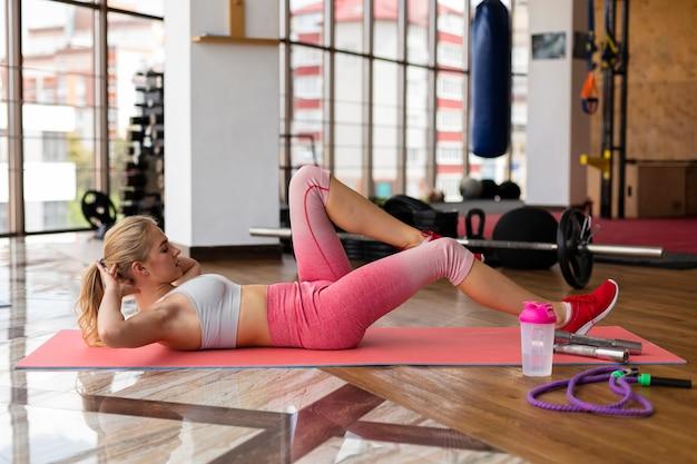 Mujer joven en rutina de ejercicios mat Foto gratis