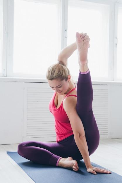Mujer joven en una sala blanca haciendo ejercicios de yoga. Foto Premium