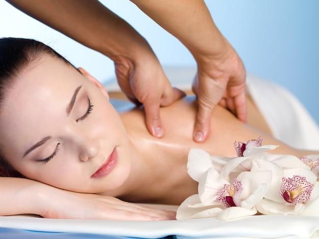 Mujer joven en el salón de spa con masaje de hombro - horizontal Foto gratis