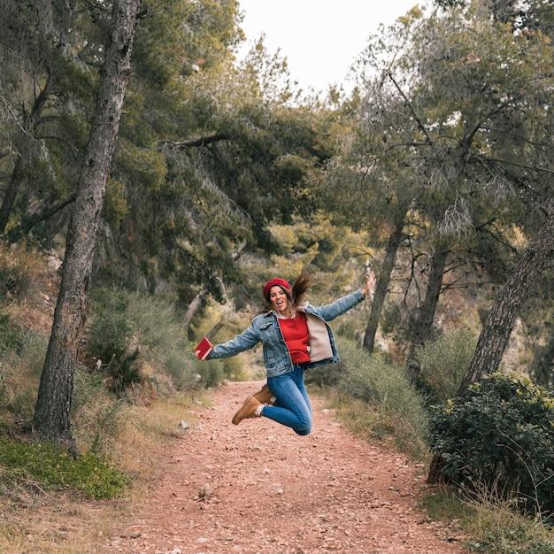 Mujer joven saltando por encima del sendero en la montaña Foto gratis