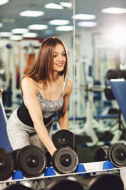 Mujer joven sana que hace ejercicios con pesas y posa delante del espejo del gimnasio Foto Premium