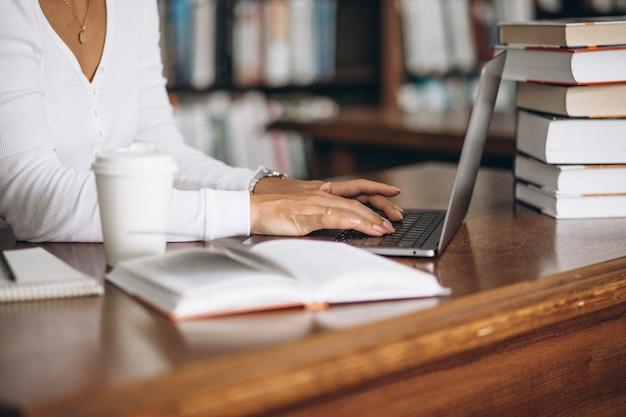 Mujer joven sentada en la biblioteca con libros y computadora Foto gratis