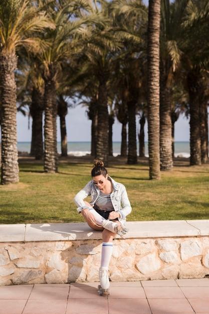 Mujer joven sentada cerca del banco que ata el cordón del patín Foto gratis