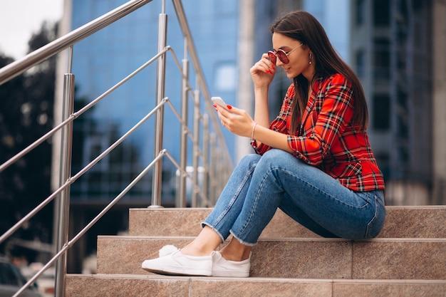 Mujer joven sentada en las escaleras y hablando por teléfono Foto gratis