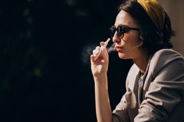 Mujer joven sentada y fumando ecigarette Foto gratis