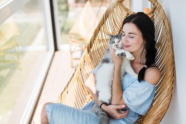 Mujer joven sentada en una silla en el patio amando a su gato mascota Foto gratis