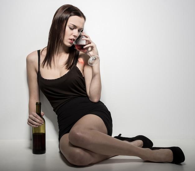 Una mujer joven está sentada en el suelo con una copa de vino. Foto Premium