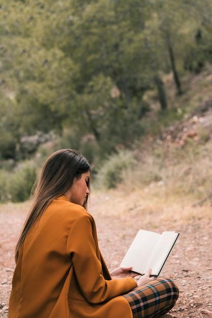 Mujer joven sentada en el suelo leyendo el libro Foto gratis