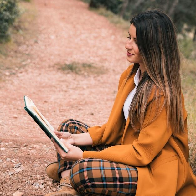 Mujer joven sentada en el suelo con las piernas cruzadas leyendo el libro Foto gratis