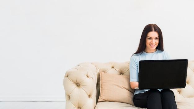 Mujer joven, sentado, con, computador portatil, en, sofá Foto gratis