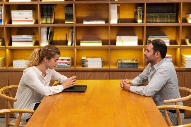 Mujer joven seria que se sienta en la entrevista y que usa el teléfono móvil Foto gratis