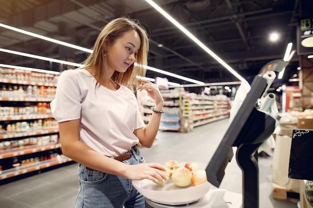 Mujer joven shoppong en supermercado Foto gratis