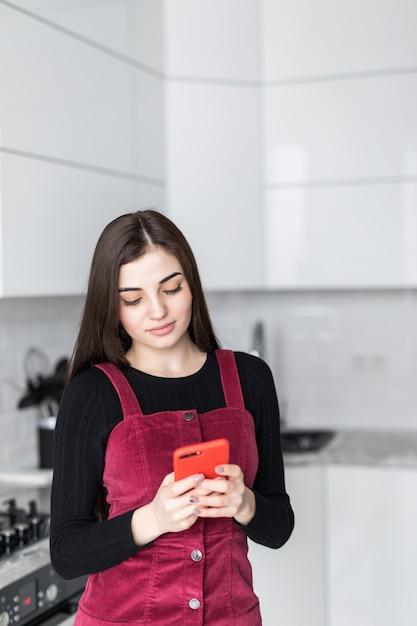 Mujer joven con smartphone apoyado en la mesa de la cocina con taza de café y organizador en un hogar moderno. mujer sonriente que lee el mensaje de teléfono. chica morena feliz escribiendo un mensaje de texto Foto gratis