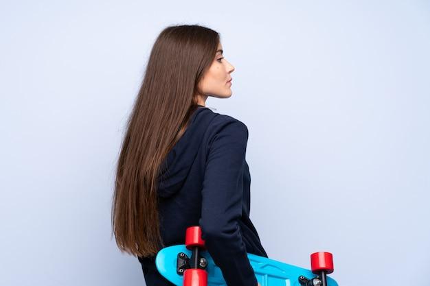 Mujer joven sobre aislado con patín en posición posterior Foto Premium