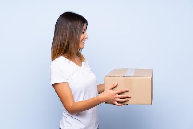 Mujer joven sobre azul aislado sosteniendo una caja para moverlo a otro sitio Foto Premium