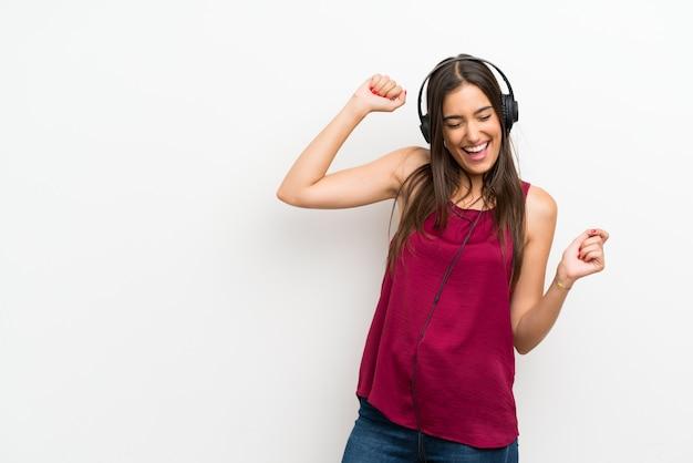 Mujer joven sobre blanco aislado escuchando música con auriculares Foto Premium