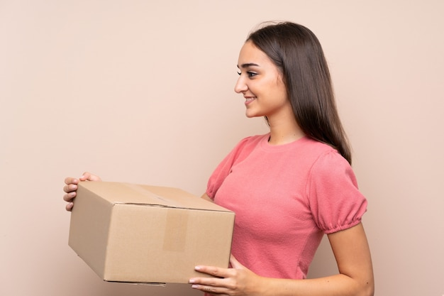 Mujer joven sobre fondo aislado sosteniendo una caja para moverlo a otro sitio Foto Premium