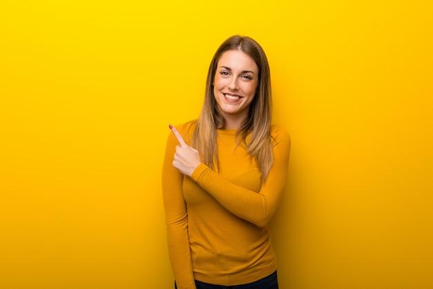 Mujer joven sobre fondo amarillo que apunta al lado para presentar un producto Foto Premium