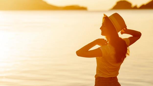 Mujer joven con un sombrero al atardecer en la orilla de un lago Foto gratis