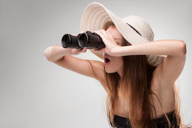 Mujer joven con sombrero con binoculares Foto gratis