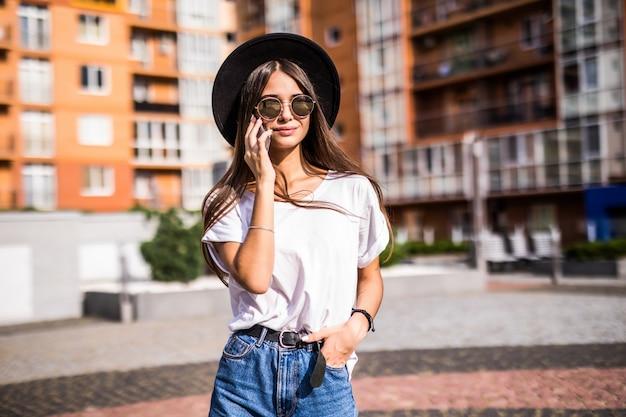Mujer joven con sombrero negro con teléfono móvil en la calle de la ciudad. chica hablando por teléfono Foto gratis