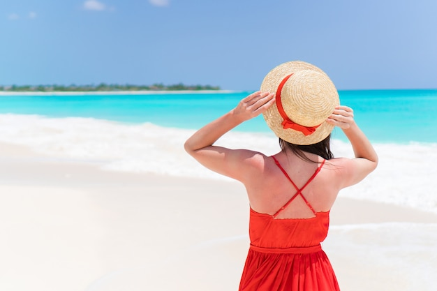 Mujer joven con sombrero durante las vacaciones de playa tropical. vista posterior de beautidul chica al aire libre Foto Premium