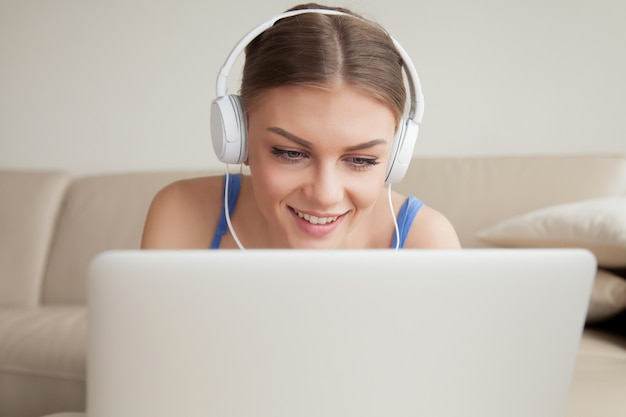 Mujer joven sonriente con auriculares usando laptop, headshot Foto gratis