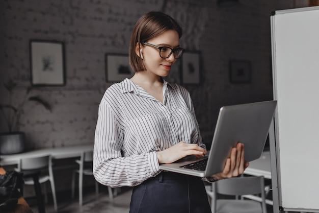 Mujer joven sonriente en blusa a rayas y gafas de montura negra mira la pantalla del portátil en el fondo de la pizarra. Foto gratis