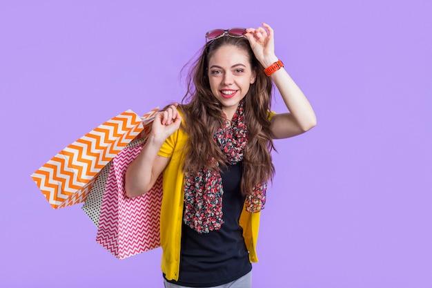 Mujer joven sonriente con los bolsos de compras contra el contexto púrpura Foto gratis