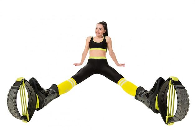 La mujer joven sonriente en kangoo salta los zapatos que sientan las piernas separadas. Foto Premium