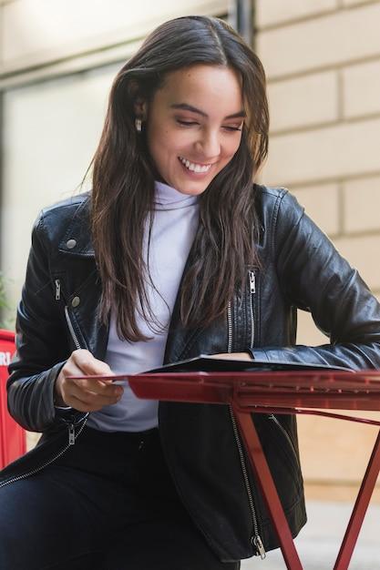 Mujer joven sonriente de moda que lee la tarjeta del menú en el café al aire libre Foto gratis