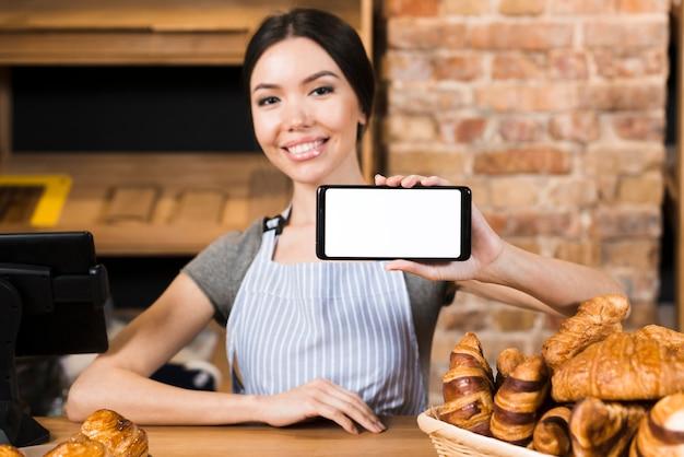 Mujer joven sonriente en el mostrador de la panadería que muestra su teléfono móvil Foto gratis