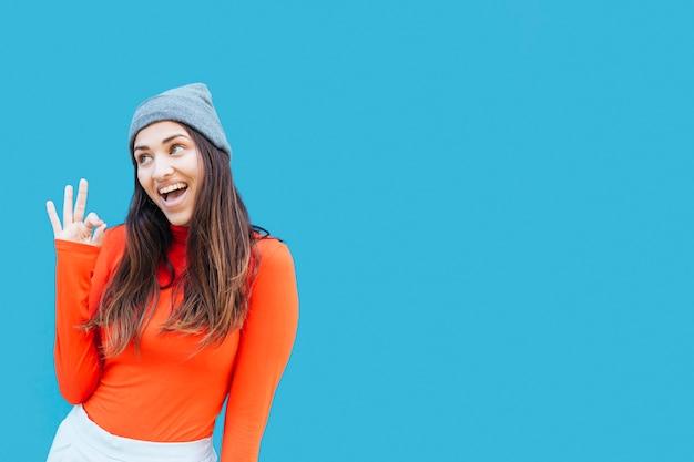 Mujer joven sonriente con la muestra aceptable que lleva el sombrero de punto delante del fondo azul Foto gratis
