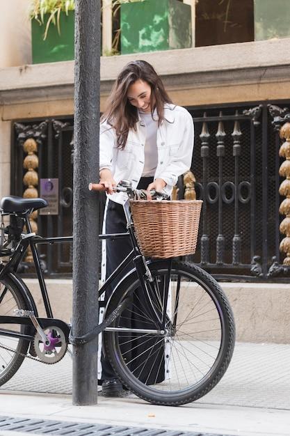 Mujer joven sonriente que se coloca cerca de la bicicleta en la acera Foto gratis