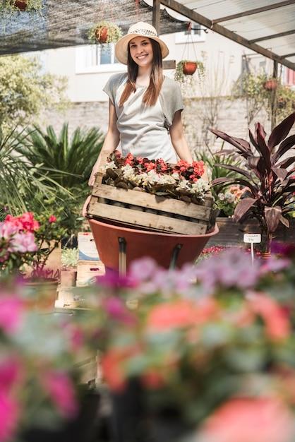 Mujer joven sonriente que lleva el cajón de flores en carretilla Foto gratis