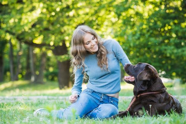 Mujer joven sonriente que mira su perro en parque Foto gratis