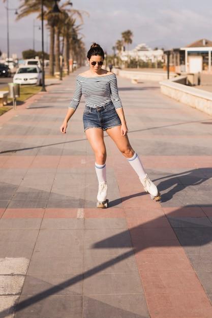 Mujer joven sonriente que patina en la acera en ciudad Foto gratis