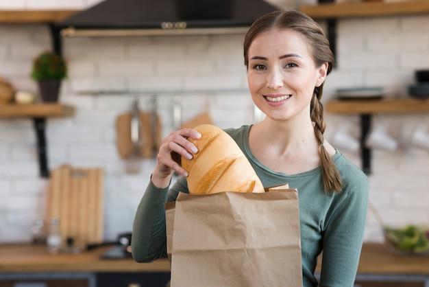 Mujer joven sonriente que sostiene el pan fresco Foto gratis