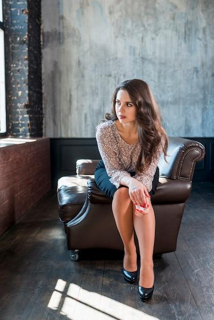 Mujer joven sospechosa sentada en el borde del sillón mirando a la ventana Foto gratis