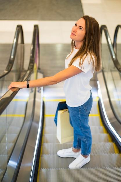 Mujer joven sosteniendo bolsas de la compra en la escalera mecánica Foto gratis