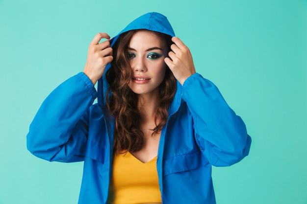 Mujer joven en streetwear ponerse capucha de impermeable o chaqueta Foto Premium