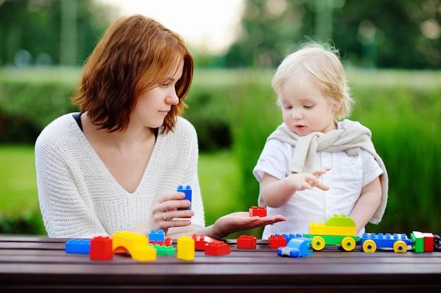 Mujer joven con su hijo pequeño jugando con coloridos bloques de plástico Foto Premium