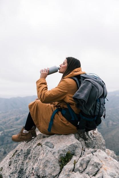 Mujer joven con su mochila sentada en la cima del pico de la montaña bebiendo el agua de una botella Foto gratis