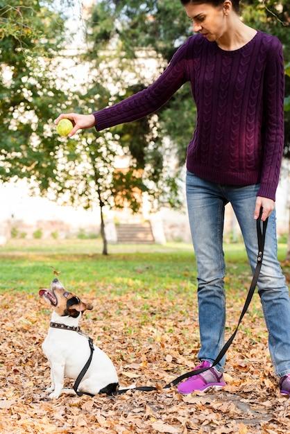 Mujer joven con su perro en el parque Foto gratis