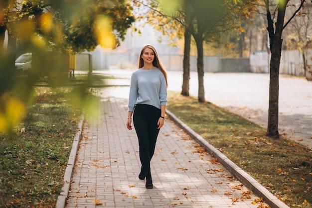 Mujer joven en suéter azul en el parque otoño Foto gratis