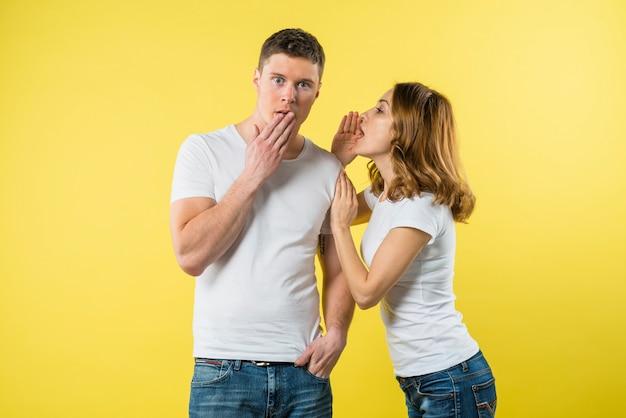 Mujer joven susurrando algo en la oreja de un novio sorprendido Foto gratis